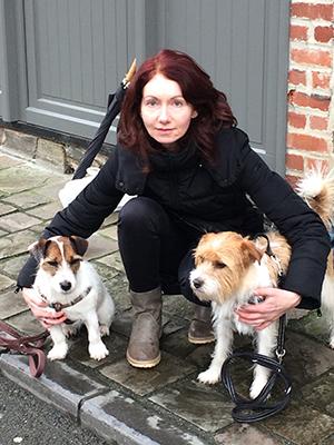 Marjolijn gehurkt bij haar twee eigen honden op de stoep